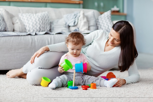 Little girl and mom play on the floor on a light carpet with bright toys, build a tower