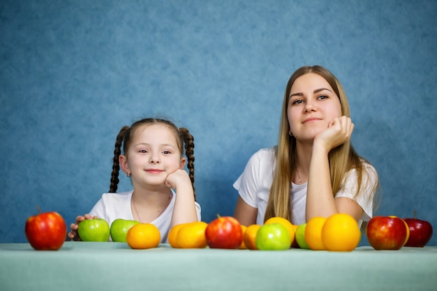 Little girl and mom play with fruits and fool around. they are wearing t-shirts