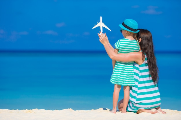 Little girl and mom with white miniature of airplane at beach