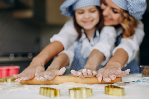 Little girl and mother roll out the dough with a rolling pin together.