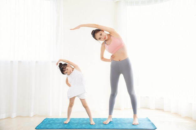 Little girl and mother sport at home