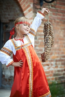 Little girl in national costumes with bast