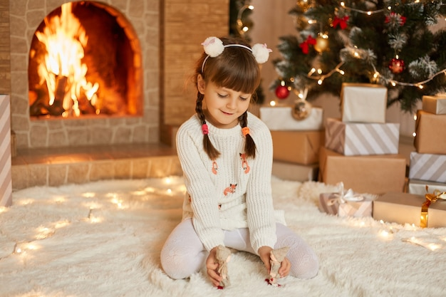 Little girl near christmas tree and fireplace playing with tiny toys