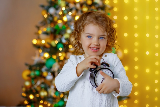 A little girl near the christmas tree holds an alarm clock