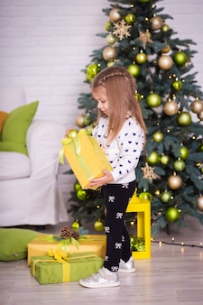 Little girl near the christmas tree opens christmas presents