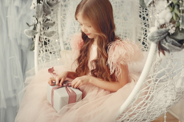 Little girl near christmas tree in a pink dress