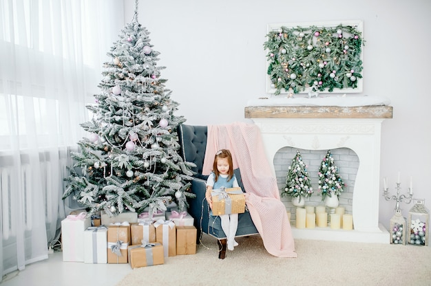 Little girl near a christmas tree with toys, next to a fireplace