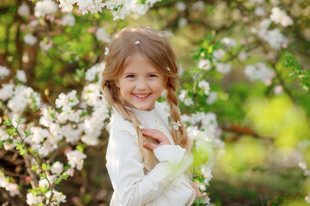 A little girl near a flowering tree in the spring garden