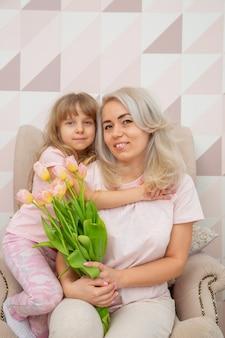 白人の外観の少女は母の日に母親を祝福し、北欧スタイルの明るいリビングルームで花束とカードを与えます