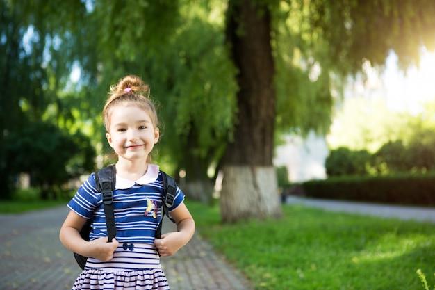 Маленькая девочка кавказской внешности в школьной форме с рюкзаком. концепция обратно в школу. начальная школа, развивающие занятия для дошкольников.