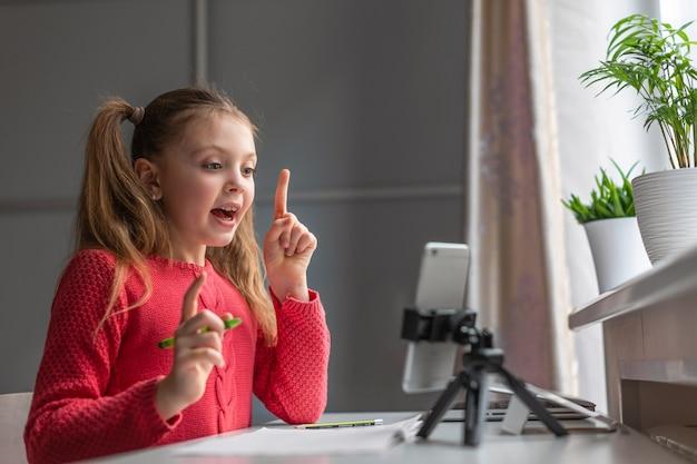 유럽식 외모의 어린 소녀는 집에서 스마트폰 화면을 미소로 바라보고 있습니다. 어린이 온라인, 기술 및 통신 개념