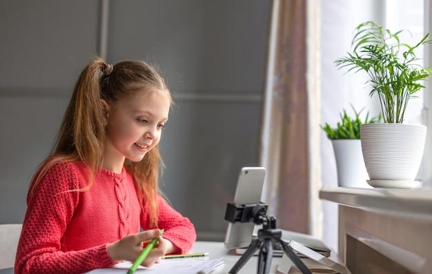 Маленькая девочка европейской внешности смотрит на экран смартфона дома с улыбкой