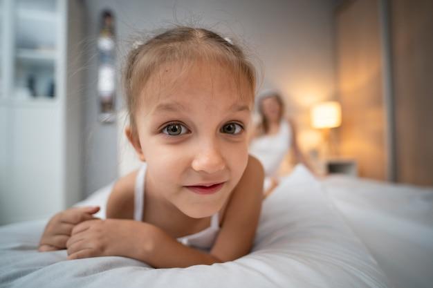 취학 전 연령 5세의 어린 소녀가 침대에 있는 침실에서 즐거운 시간을 보내고 있습니다.