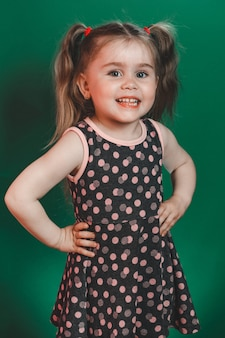Маленькая девочка трех лет с хвостами в платье позирует в студии на зеленом фоне 2021