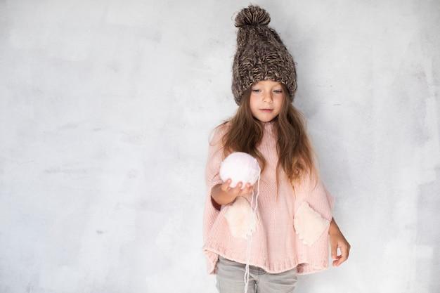 Маленькая девочка предлагает снежок