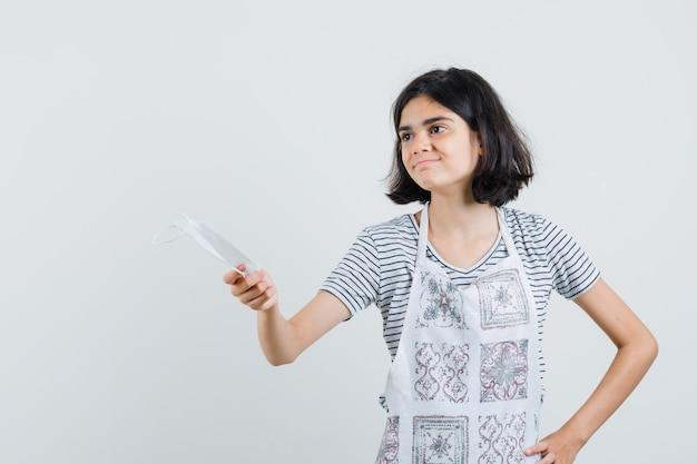 Bambina che offre mascherina medica e sorridente in t-shirt, grembiule,