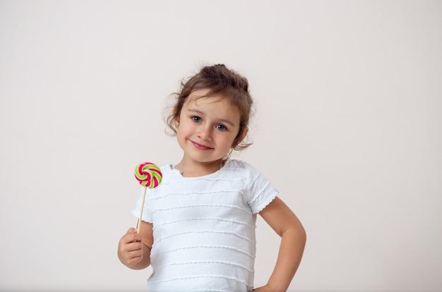 Маленькая девочка на ярком фоне стоит с леденцом в руке и улыбается.