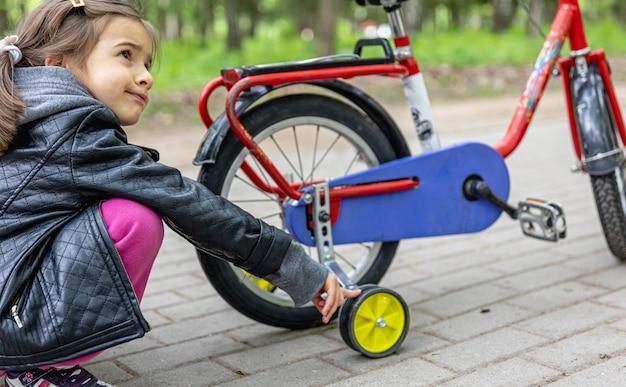 Маленькая девочка на прогулке в парке со своим велосипедом.