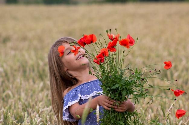 Маленькая девочка на пшеничном поле с красными маками.