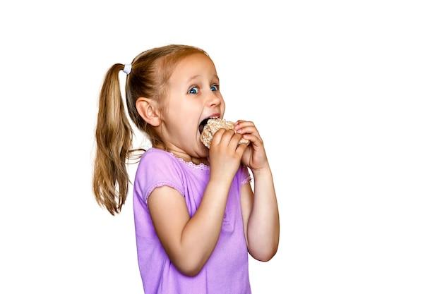 흰색 배경에 있는 어린 소녀는 쿠키 라운드 밥을 먹는다