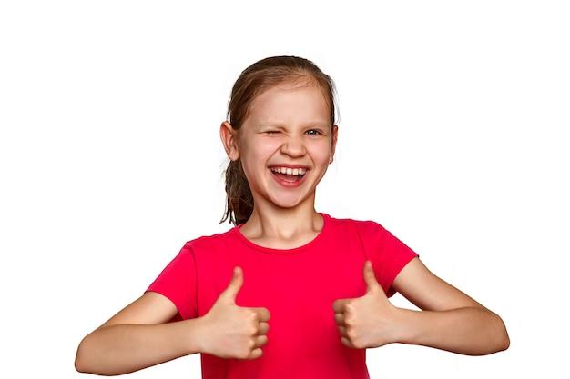白い背景の上の少女は親指を立てる