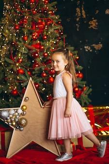 クリスマスツリーのそばに立っているピンクのドレスでクリスマスの少女