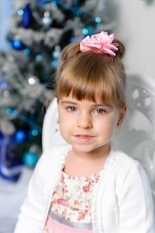 クリスマスツリーの背景に小さな女の子。