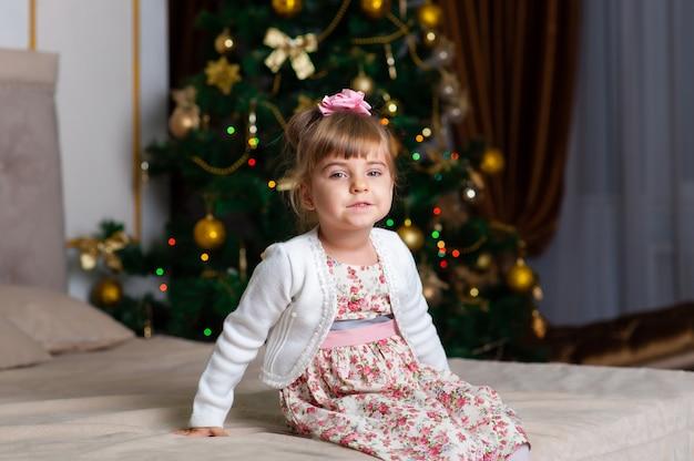 Маленькая девочка на фоне рождественской елки.