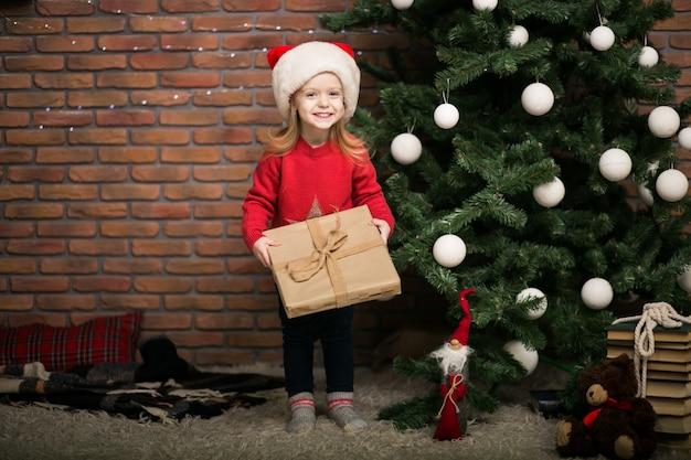 クリスマスツリーのギフトボックスを持つクリスマスの小さな女の子