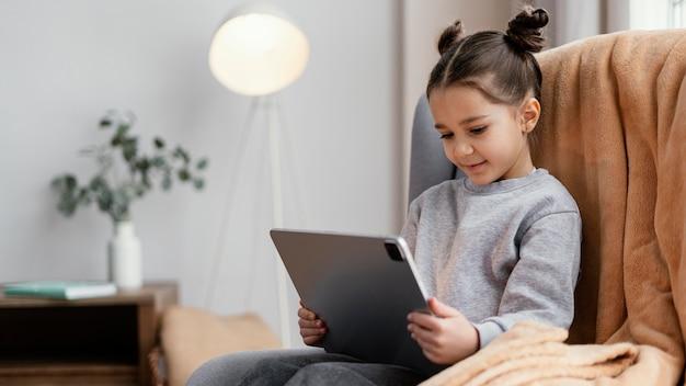 태블릿을 사용 하여 소파에 어린 소녀
