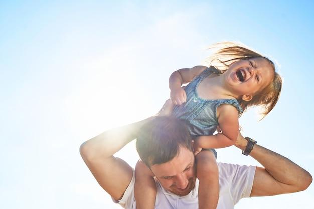 Маленькая девочка на плечах папы.