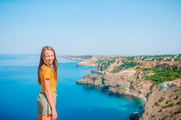 절벽의 가장자리에 어린 소녀는 산 정상 바위에서 경치를 즐길 수