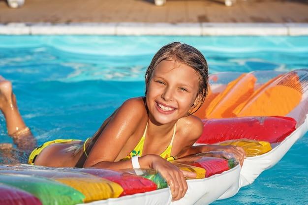 수영 풀에서 팽창 식 매트리스에 어린 소녀입니다. 웃는 아이가 놀고 수영장에서 재미