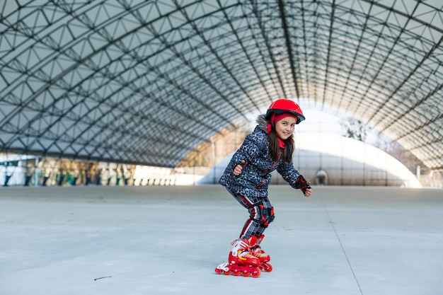 봄에 도시에서 롤러 스케이트를 탄 어린 소녀
