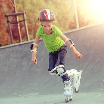 夕暮れ時の公園でヘルメットをかぶったローラー スケートの少女