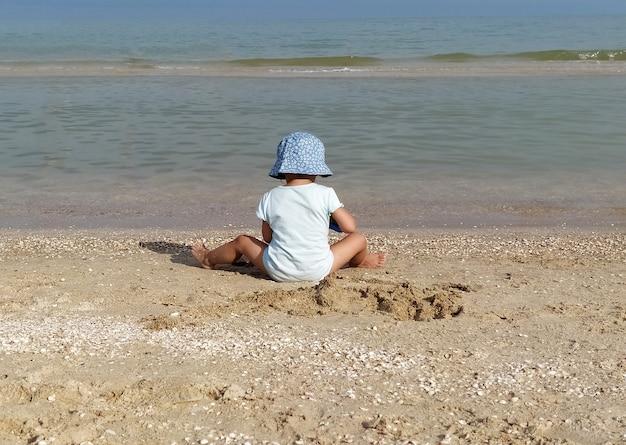 Маленькая девочка на пляже, играя с песком