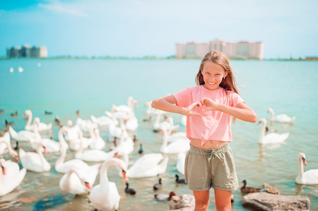 Маленькая девочка на пляже с красивыми лебедями