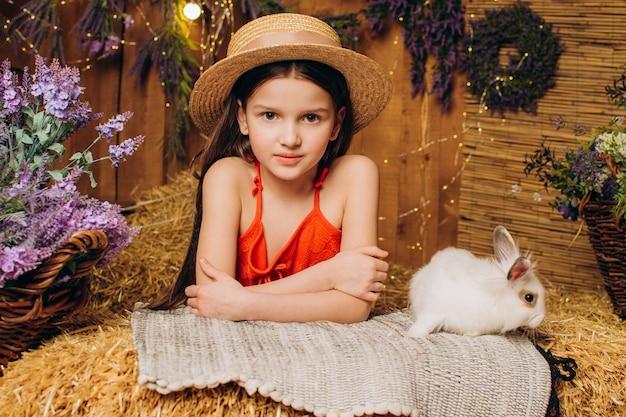 농장에 있는 어린 소녀는 토끼 부활절 휴가 개념과 함께 앉아 있습니다.
