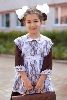 Маленькая девочка на улице в винтажной форме с портфелем