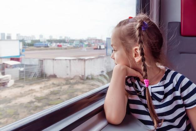 電車の中で小さな女の子が窓の外に見える