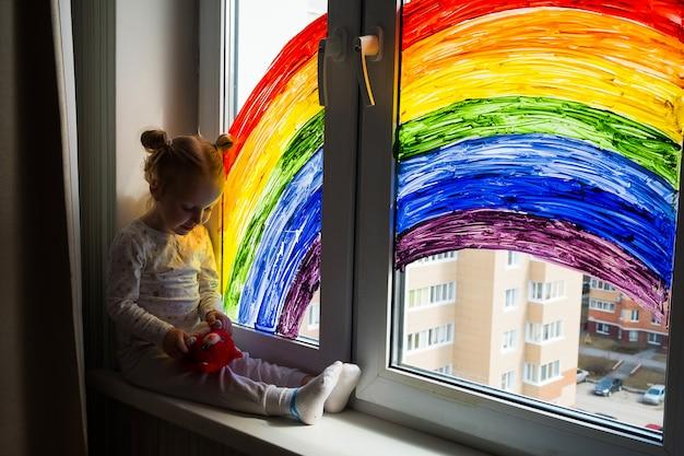 Маленькая девочка на стене картины радуги на окне. детский досуг дома. положительная визуальная поддержка во время карантинного пандемического коронавируса covid-19 в домашних условиях.