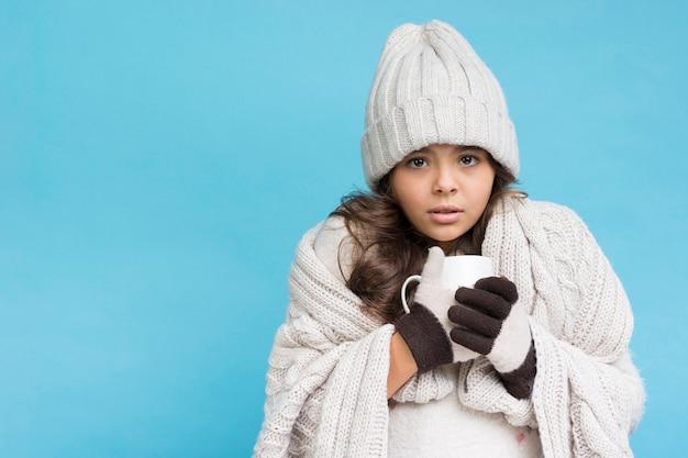 뜨거운 차 복사 공간을 마시는 겨울에 어린 소녀