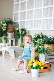 春の花と木製のベンチに小さな女の子。