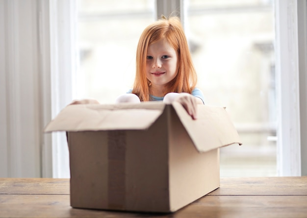 Little girl opening a box