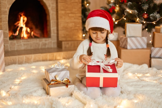 Little girl opening christmas present, keeping fingers on ribbons, looking at gift box with smile, child wearing santa claus hat posing on floor near fireplace and xmas tree.