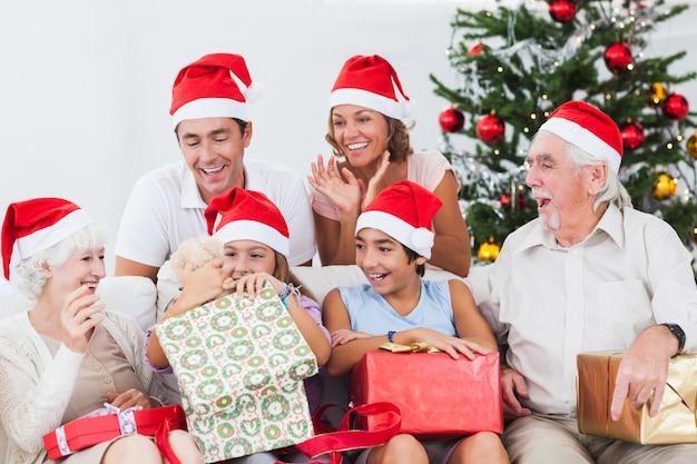 クリスマスプレゼントを開いている少女 Premium写真