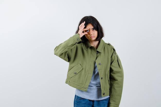 Occhio di apertura della bambina con le dita in cappotto, t-shirt, jeans e dall'aspetto carino, vista frontale.