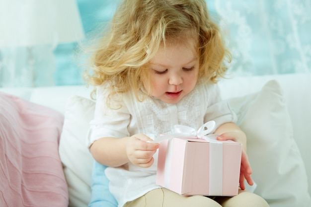 Little girl opening a gift