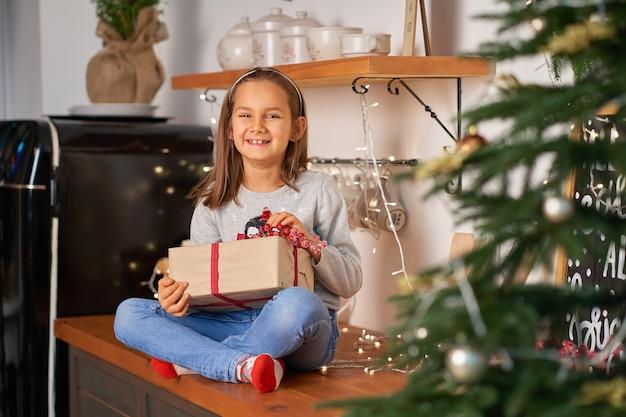 小さな女の子はサンタからのクリスマスプレゼントで箱を開けます。