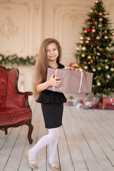 A little girl opens a christmas present from santa. christmas tale. happy childhood.